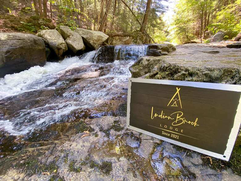 indian brook lodge sign by a brook