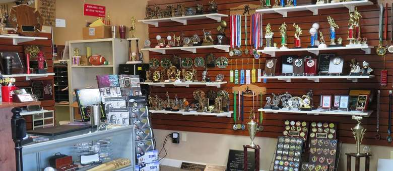 trophies and awards on a wall in a store
