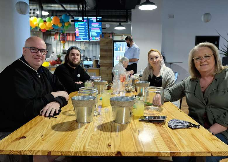 two women and two men around a table in a food hall
