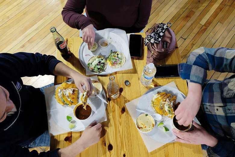 three people around a table eating tacos