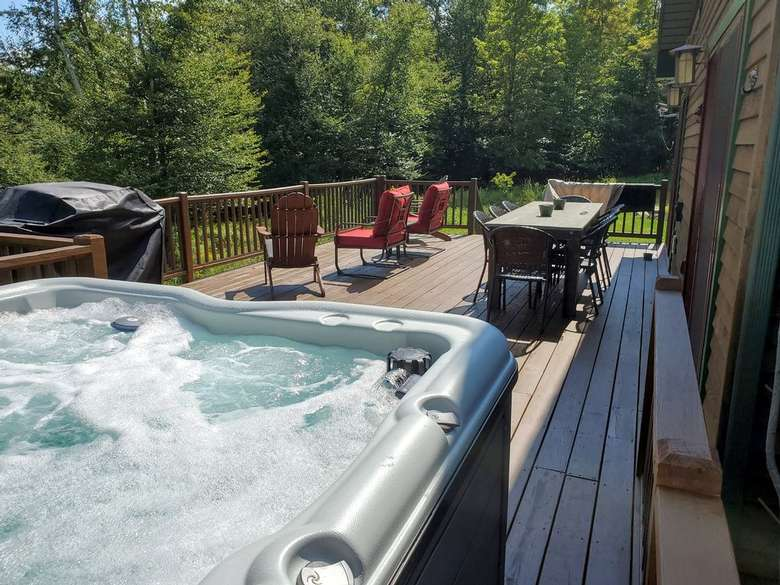 hot tub, chairs, and table on a deck