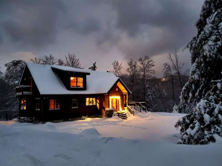 a cabin with lights on during winter with snow on the ground