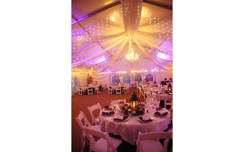 Reception tent with colorful uplighting.