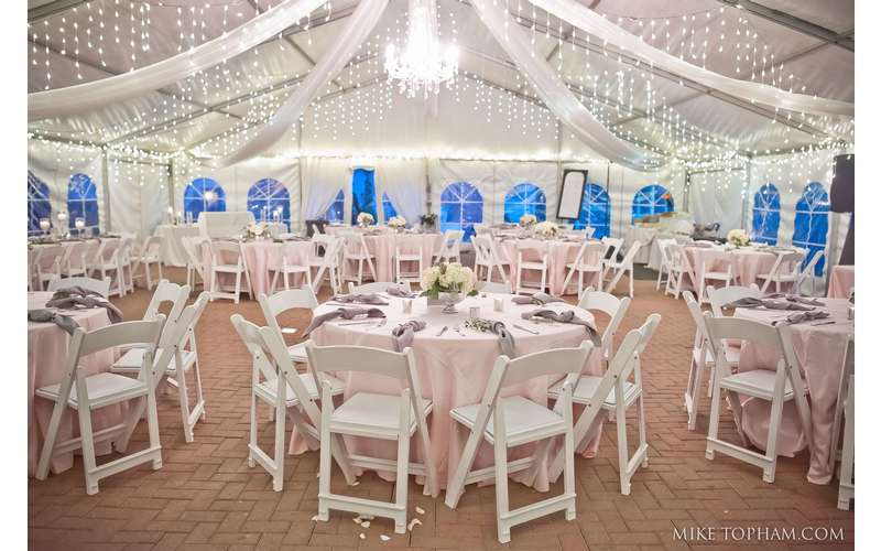 Our reception tent includes perimeter lights, icicle lights, chandelier, and drapery. Photo by Mike Topham Photography