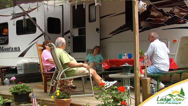 four people sitting in chairs near their RV and campsite