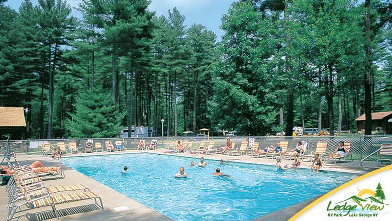 tall green trees around an outdoor pool, and there are people both swimming and sitting near the pool