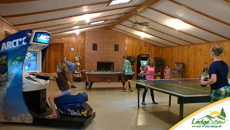 a rec room with arcade machines and a ping pong table
