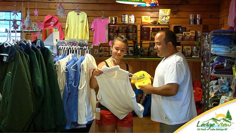 two people in a gift shop filled with clothes and other items