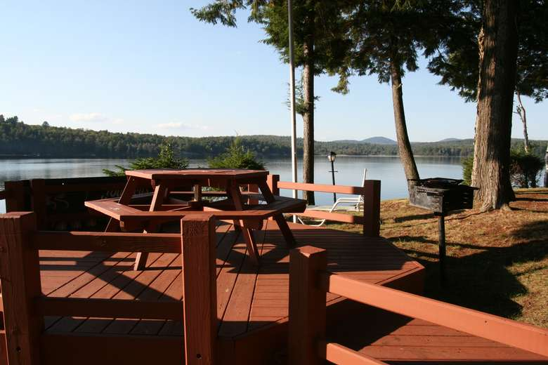 deck picnic area and charcoal grill with lake in background