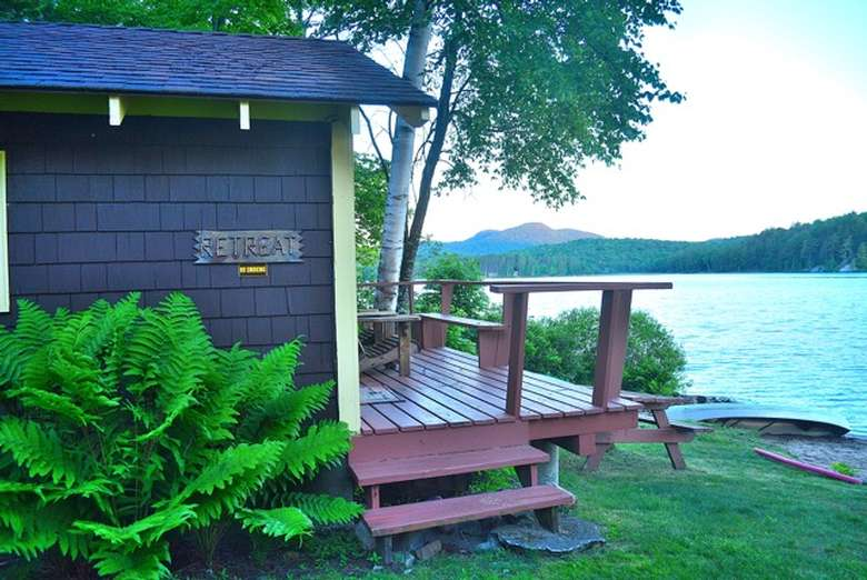 front deck of cabin in close proximity to beach and lake