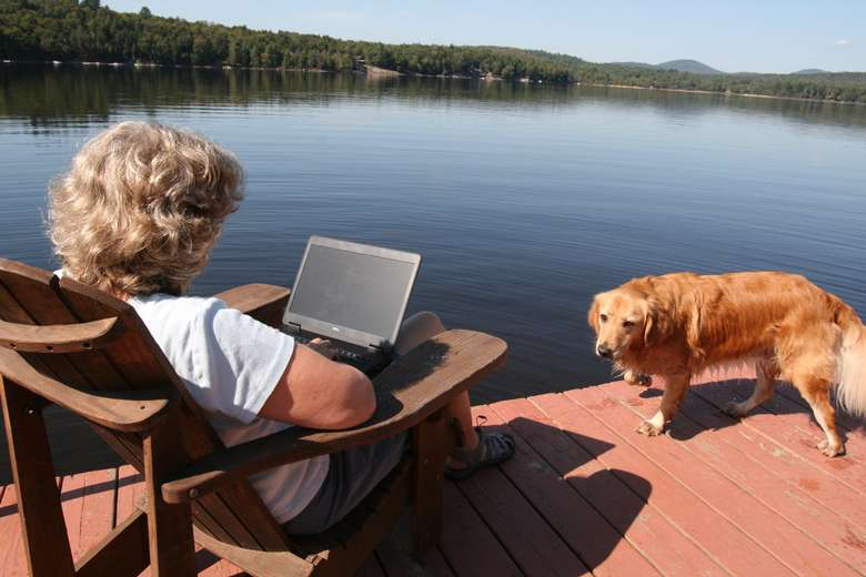 woman sitting in chair using laptop by the lake with golden retriever by her side