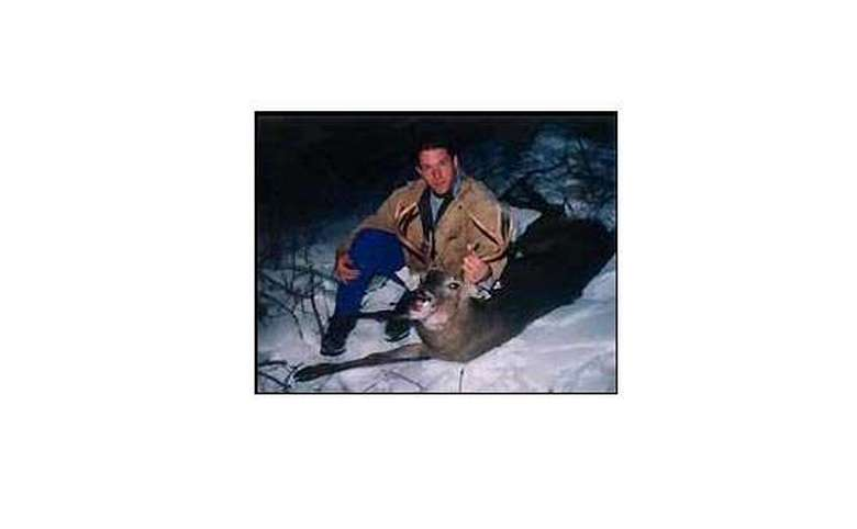 Man sittting in the snow with a single deer holding its head up by the horns