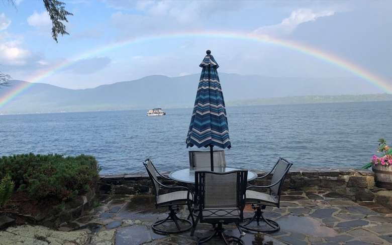 stone patio on the lake with an outdoor table, surrounded by four chairs, with an umbrella. There is a large rainbow forming an arc over the lake, with mountains in the distance