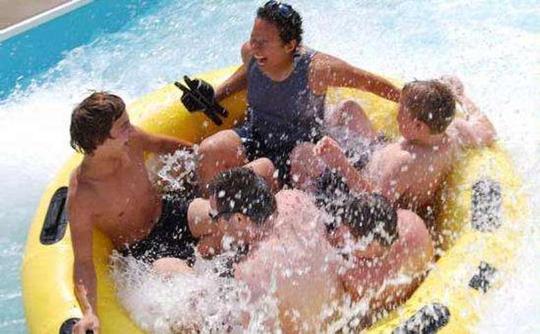 family of five in raft with splashing water