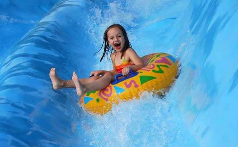 laughing young girl on yellow tube on water slide ride