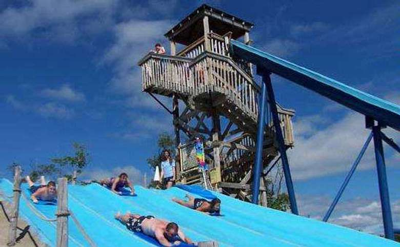 looking up towards water slide ride and riders sliding down hill