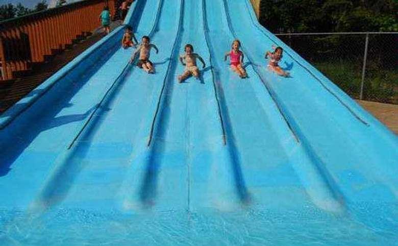 five kids sliding down water slide