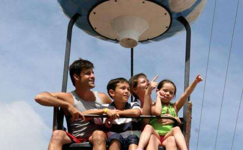 mother, father and two kids on sky ride shaped like hot air balloon