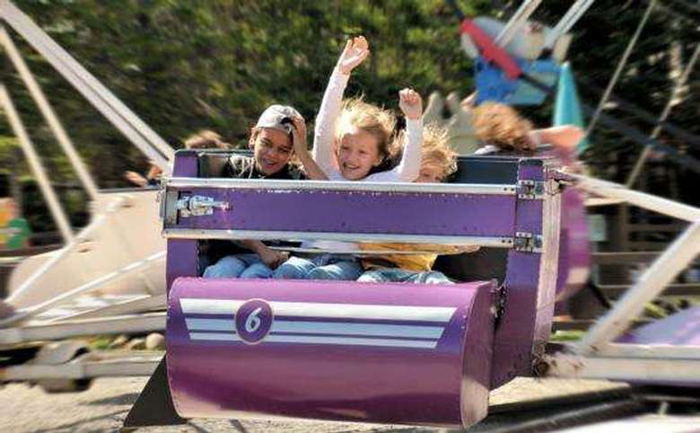 three young children laughing in cab of amusement park ride