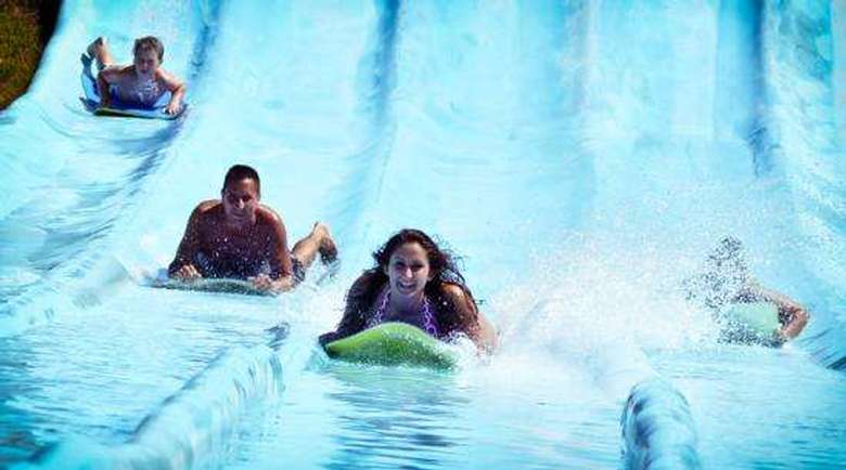 a family riding individual rafts down water slide