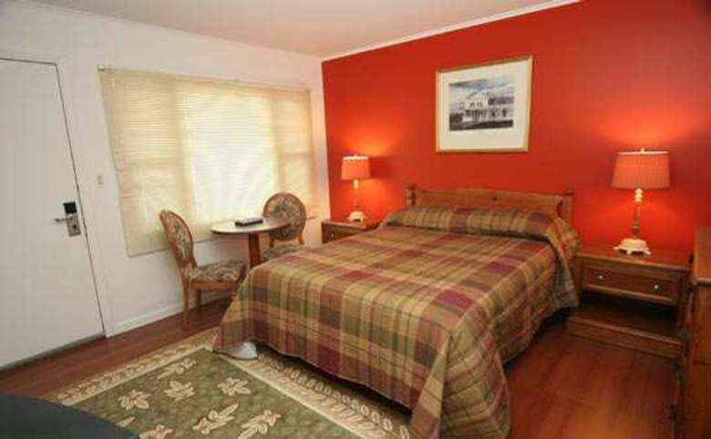motel room with a king size bed in front of a red accent wall