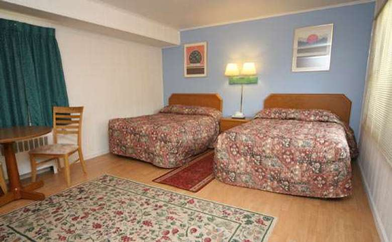 motel room with two double beds in front of a blue accent wall