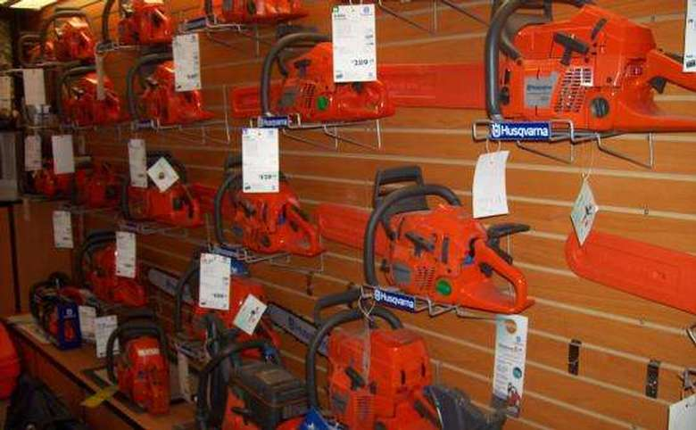 orange chainsaws hanging on a wall