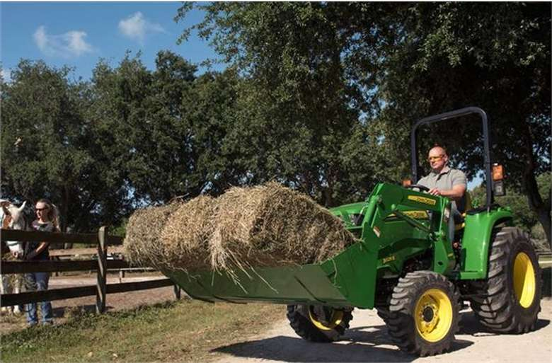 a green tractor with hay in the front bucket
