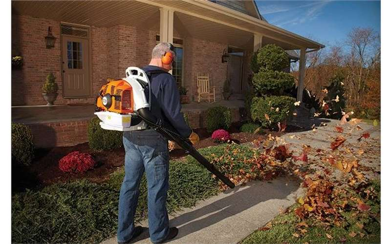 a man with a leaf blower on his back