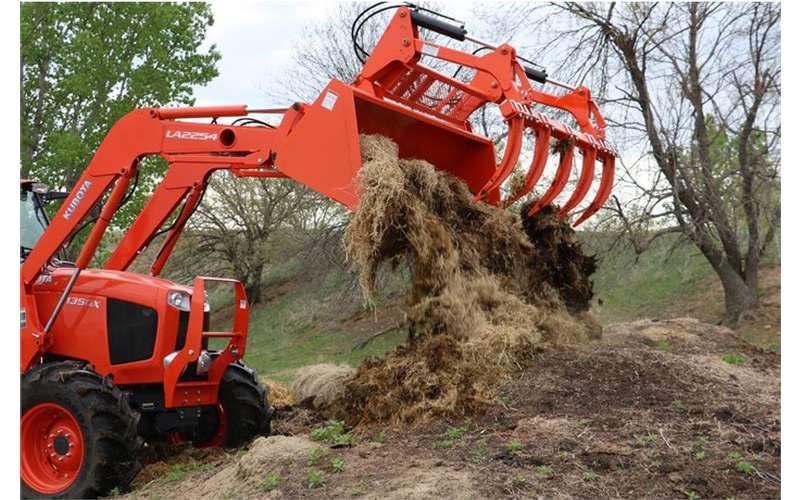 a big red grapple bucket dumping dirt