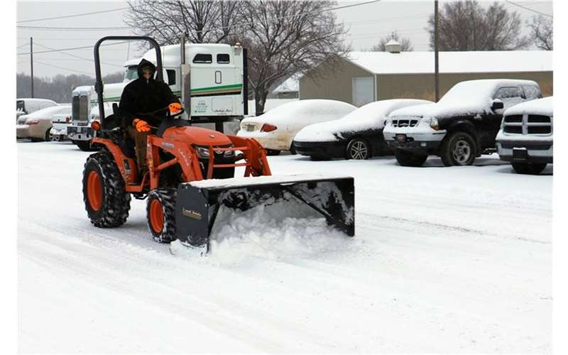 a person driving a small orange snow plow in winter