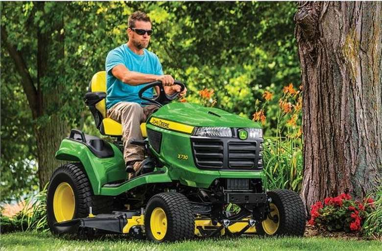 a green lawn mower being driven by a man wearing sunglasses