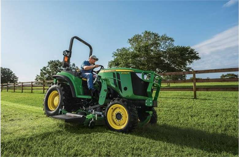 a large green tractor and lawn mower on grass