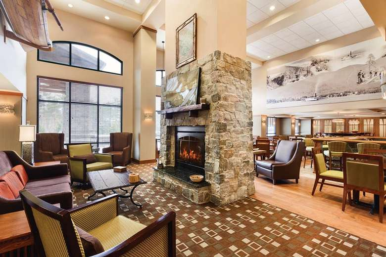 lobby filled with chairs, tables, and a fireplace