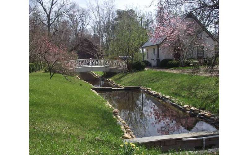 a small river and bridge on the property lawn
