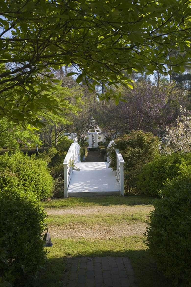 a white bridge leading to the gardens