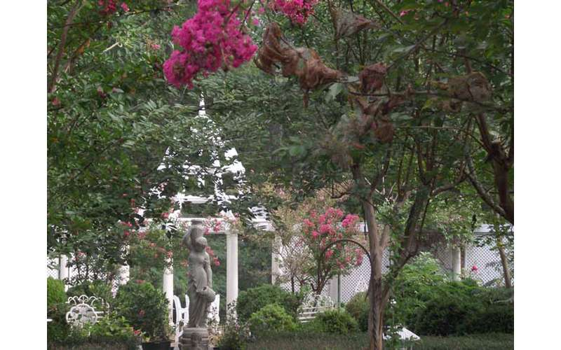 a view of beautiful gardens with a statue and white structure in the background