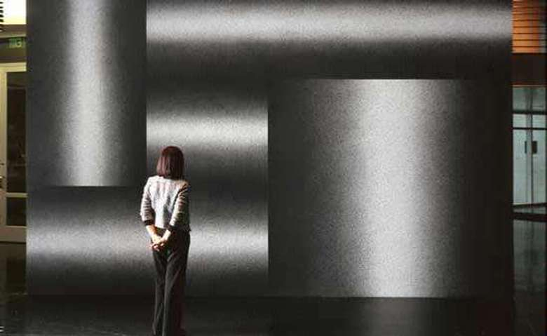 woman standing in front of a large piece of art that looks like five metal pipes