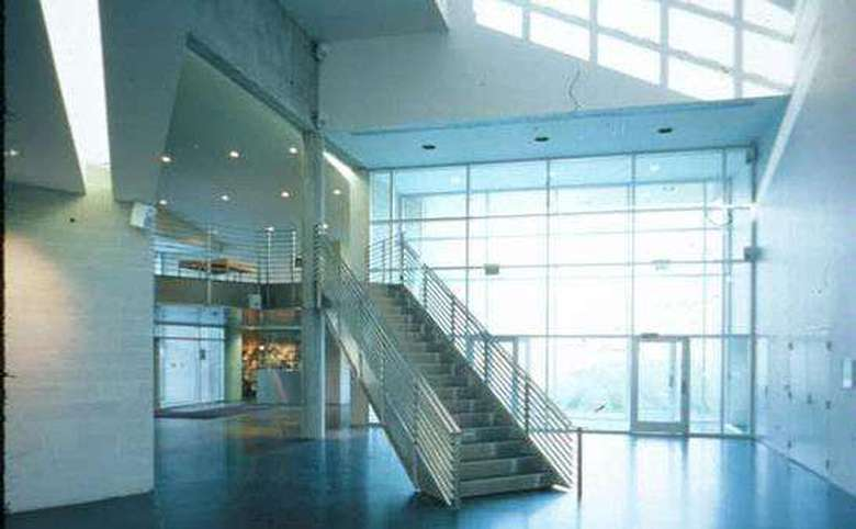 museum lobby with large glass windows and doors, plus a modern looking stairway leading up to the second floor