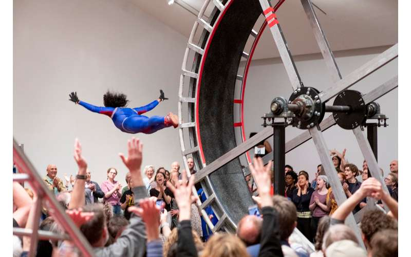 A female acrobat flies off a giant wheel in the Tang Museum