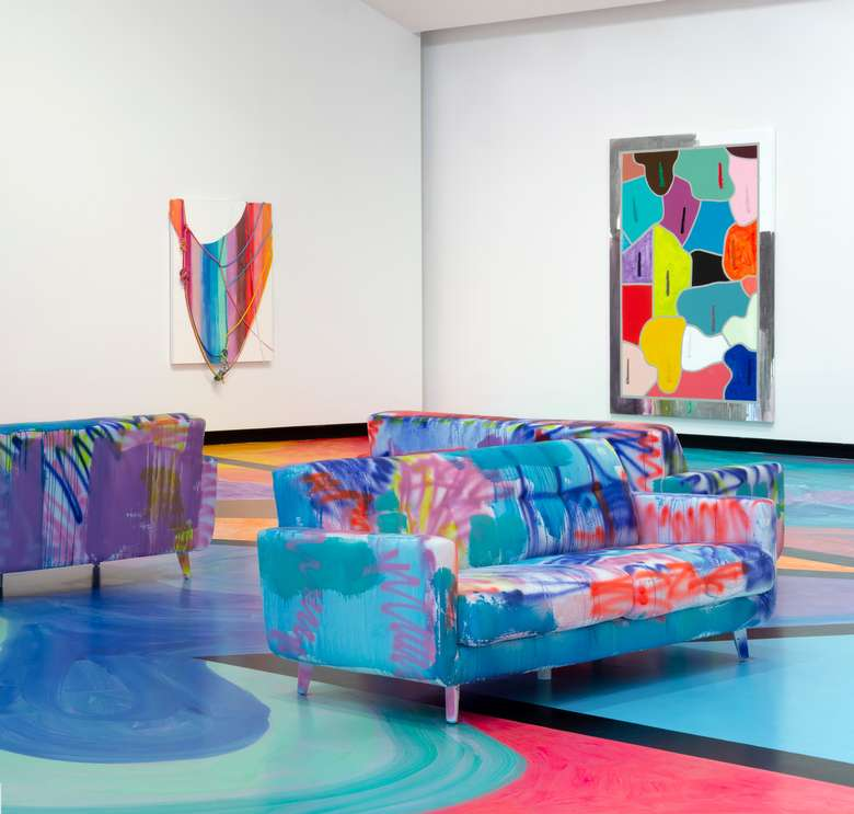 Colorful painted couches and floors in an art gallery with colorful paintings on the walls