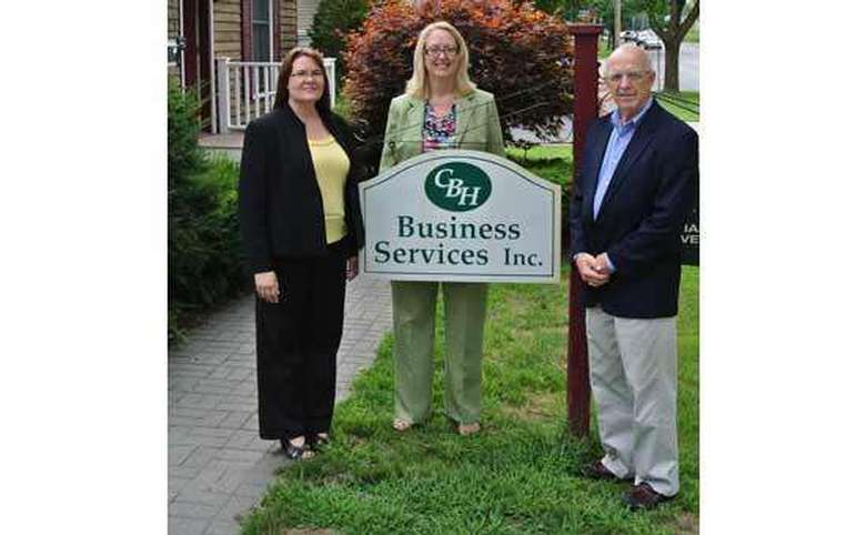 two women and one man in front of a business services sign outside
