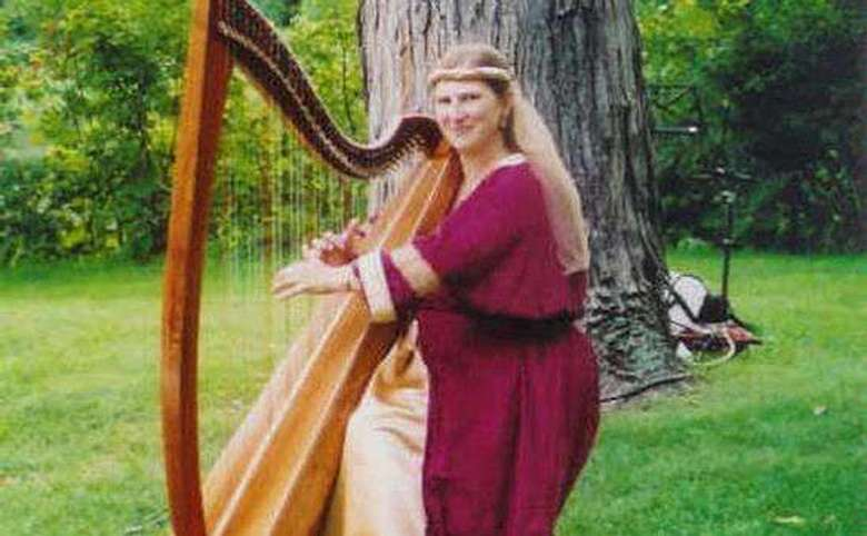 woman in a red robe playing the harp