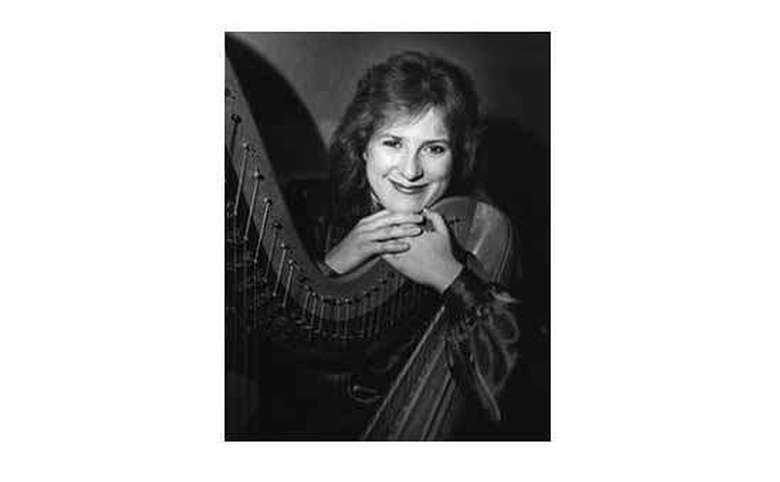 black and white photo of a woman posing with a harp