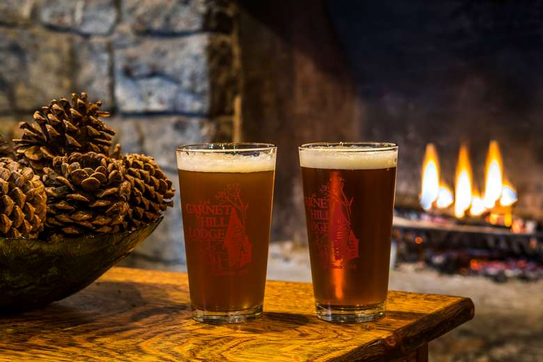 two pint glasses of beer on a table in front of the fireplace