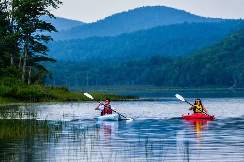 two kayakers on the lake with mountains in the background