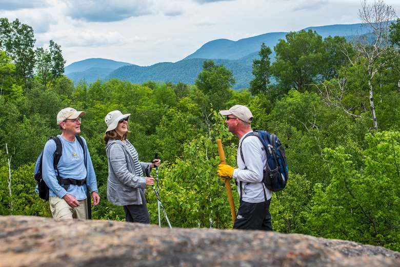 three hikers on mountain trail