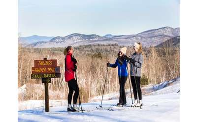 three cross country skiers on snowy slope near a trail sign