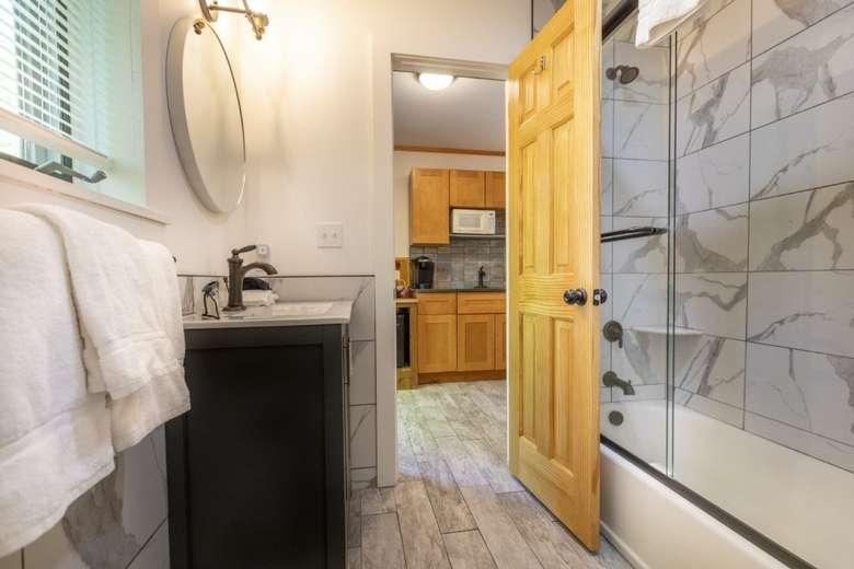 bathroom with door open and view of sink and shower