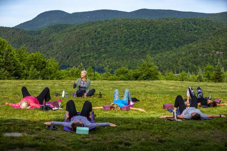 people doing yoga outdoors with view of mountains in the back